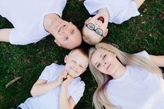Overhead portrait on family lying on grass in park. Happy family in the park Royalty Free Stock Photo