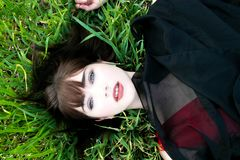 Overhead view of beautiful woman lying in grass looking at camera royalty free stock photography