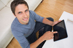 Overhead portrait of man using digital tablet in living room Stock Image