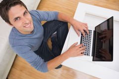 Overhead portrait of a man using laptop in living room Stock Image