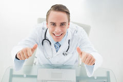 Overhead portrait of smiling doctor with laptop gesturing thumbs up Stock Photos