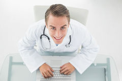 Overhead portrait of a smiling doctor using laptop Stock Image