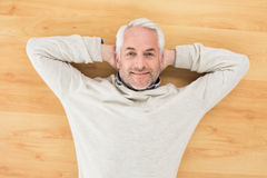 Overhead portrait of a smiling man lying on parquet floor. Overhead portrait of a smiling mature man lying on parquet floor at home Royalty Free Stock Image
