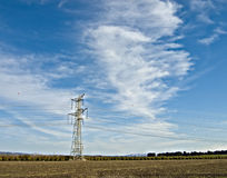 An overhead power line. In a farmland Royalty Free Stock Photo