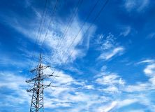Overhead power line at clouds background. Perspective view of overhead power line with electrical wires forming frame with copy-space at blue sky background royalty free stock images