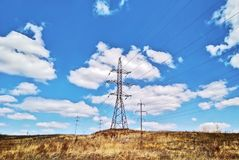 Overhead power line at sky background. Overhead power line in summer day in the field at blue sky background stock photography