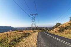 Overhead Pylon and Powerlines Next to Asphalt Road Royalty Free Stock Images