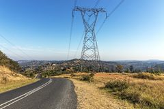 Overhead Pylon and Powerlines Next to Asphalt Road Stock Photography