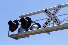 Overhead Railroad Signal And Sign Cantilever. A pair of railroad crossing signal lights and railroad crossing buck sign on an overhead metal cantilever against a Stock Image