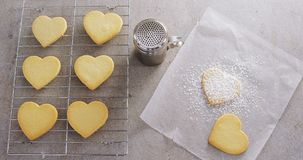 Raw heart shape cookies on baking tray with flour shaker strainer and wax paper 4k. Overhead of raw heart shape cookies on baking tray with flour shaker strainer stock footage