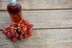 Overhead of red bunch of grapes with bottle of red wine. On wooden table stock photography
