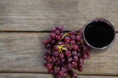 Overhead of red bunch of grapes with glass of red wine. On wooden table Royalty Free Stock Photos