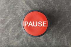 Overhead of Red Pause Push Button on Concrete Background. Overhead of a red pause push button on concrete background stock images