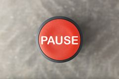 Overhead of Red Pause Button Over Blurred Gray Background. Overhead of a red pause push button over a blurred gray background stock photo