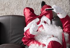 Overhead of Santa Claus relaxing in sofa at home Using cell phone for communication and leisure. Having a videocall or taking a s. Overhead of Santa Claus or royalty free stock image