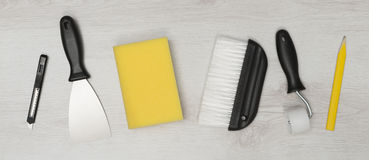 Set of Wall Paper Home Improvement Tools on Wooden Surface Royalty Free Stock Photography