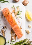 Fresh green asparagus and raw salmon fillet. Overhead shoot with fresh green asparagus, raw salmon fillet, herbs and sauce and old white wooden board. Healthy Stock Photo