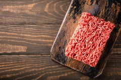 Fresh raw beef minced meat. Overhead shoot of fresh raw beef minced meat on dark wooden board. Healthy food ingredients concept with copy space. Top view Royalty Free Stock Images