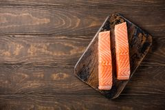 Fresh raw salmon fillet, flat lay. Overhead shoot of fresh raw salmon fillet. Old wooden background. Top view. Copy space Stock Photos