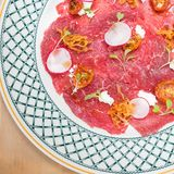 Overhead shot of a beef carpaccio with radishes. stock image
