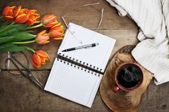 Garden Planner with Flowers and Coffee. Overhead shot a bouquet of an open book or garden planner, glasses, coffee, sissors and flowers over a wood table top Stock Images