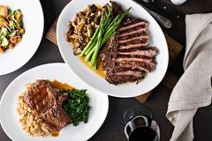 Overhead shot of a dinner table with steak and grilled pork. Overhead shot of a dinner table with sliced steak and grilled pork stock images