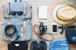 Overhead shot of essentials for traveler. Outfit of young man traveler, camera, mobile device, sunglasses. Stock Image