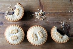 Overhead shot of four mince pies, a traditional Christmas dessert, arranged neatly on a wooden table with two partly eaten. Copy stock image