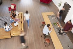 Overhead Shot Of Friends Cooking Meal And Relaxing Together Stock Image
