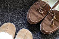 Overhead shot of generic ladies and mens slippers on a dark gray. Carpet Royalty Free Stock Photo