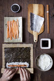 Overhead shot of hands rolling sushi and ingredients on table Stock Image