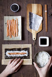 Overhead shot of hands rolling sushi and ingredients on table Stock Photo