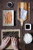 Overhead shot of hands rolling sushi and ingredients on wooden table Royalty Free Stock Image