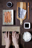 Overhead shot of hands rolling sushi and ingredients on wooden table Stock Photos
