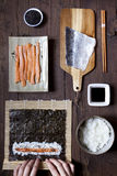 Overhead shot of hands rolling sushi and ingredients on wooden table Royalty Free Stock Photography