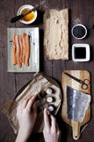 Overhead shot of hands slicing a roll of hosomaki sushi and ingredients on table Royalty Free Stock Images