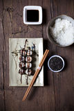Overhead shot of hosomaki sushi on plate with soy sauce and ingredients on table Royalty Free Stock Photos