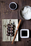 Overhead shot of hosomaki sushi on plate with soy sauce and ingredients on table Stock Photo