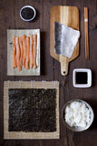 Overhead shot of ingredients for preparing sushi on wooden table Stock Photos