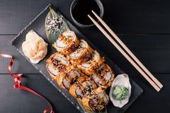 Overhead shot of Japanese sushi on black wood background. royalty free stock images