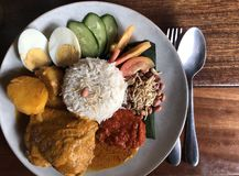 Overhead shot of Malay coconut rice dish. Overhead shot of traditional Malay nasi lemak dish on a wooden table stock photo