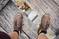Overhead shot of a male feet standing on a wooden bridge wearing hiking shoes royalty free stock images
