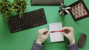 Overhead shot of man holding pen near notepad while sitting by table with chroma key stock video footage