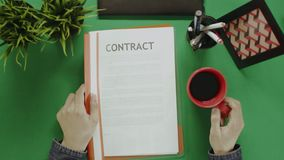 Overhead shot of man reading contract while drinking coffee stock footage