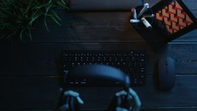 Overhead shot of man typing on keyboard and putting on headphones. Top down view of man sitting by office wooden table and typing on keyboard and putting on stock video footage