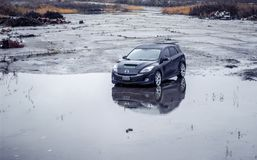 A Black 2010 Mazdaspeed3 n an abandoned wet parking lot stock photography