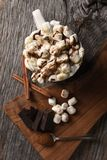 Overhead shot of a mug of hot cocoa with toasted marshmallows next to a cutting board with chocolate chunks and cinnamon sticks. royalty free stock photos