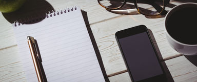 Overhead shot of notepad and smartphone Stock Photos