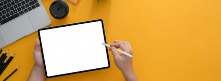 Free Overhead Shot Of Freelancer Writing On Blank Screen Tablet With Stylus On Yellow Worktable Stock Photos - 183361333