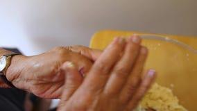 Woman makes dough balls for pizzelles. An overhead shot of an older woman making dough balls for pizzelles stock video footage
